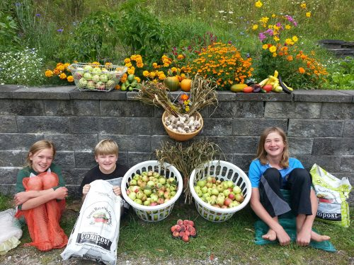 Three kids sit against rock wall surrounded by fruits, vegetables, and flowers.