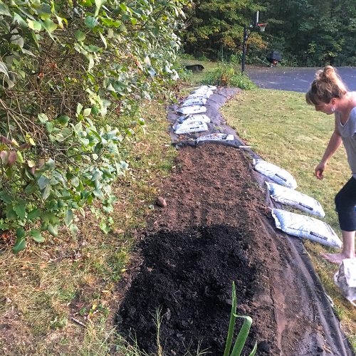 Woman adds compost to long row of soil.