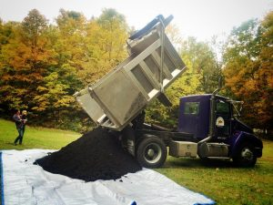 Delivery truck dumps compost onto a tarp.