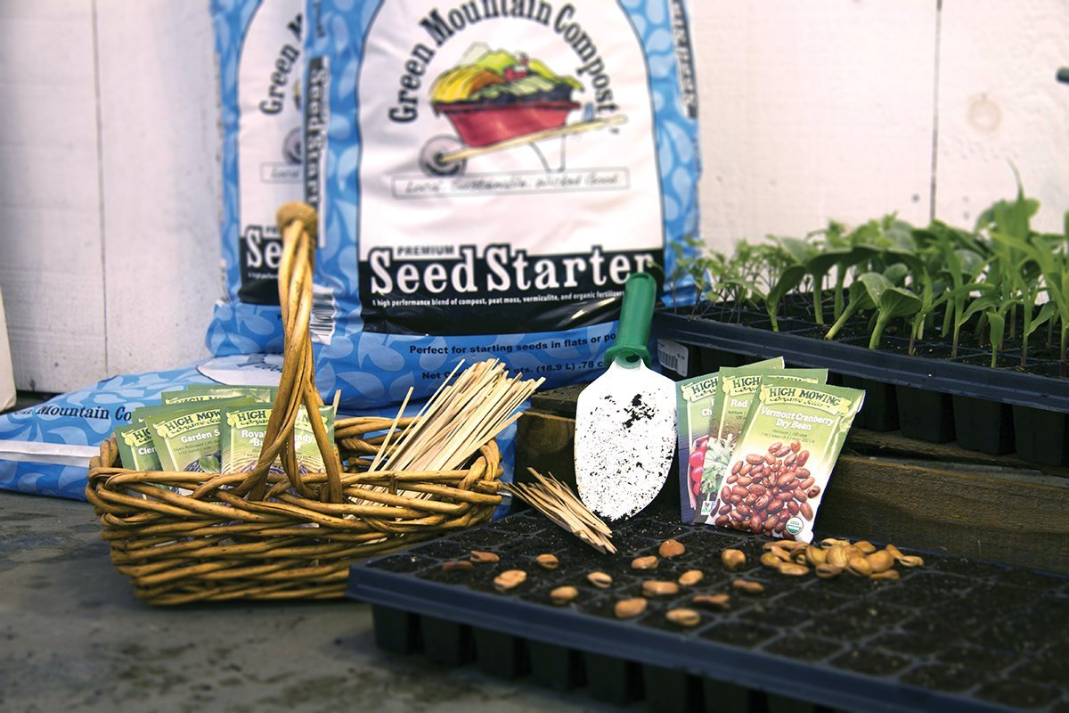 Seed tray next to wooden basket with seed packets, both in front of a bag of Green Mountain Compost Seed Starter.